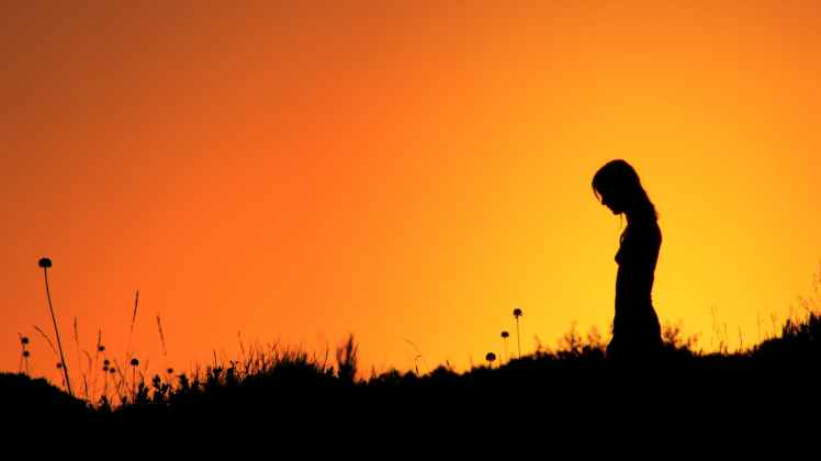 silhouette of woman standing on grass field during sunset