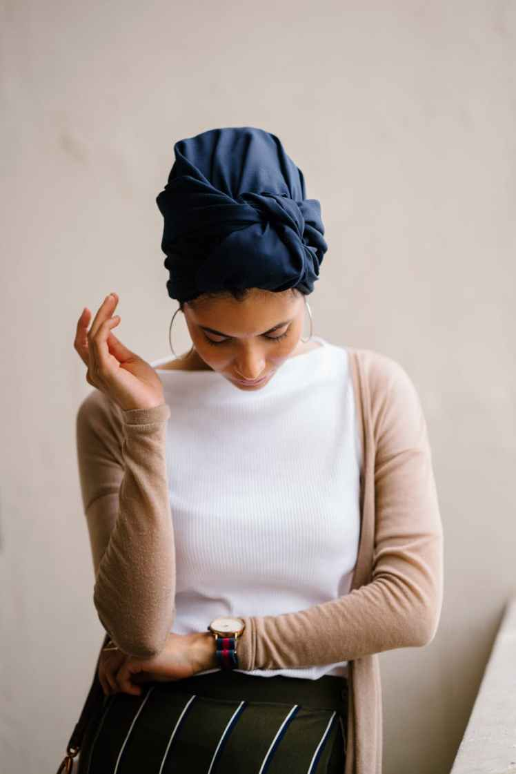 woman wearing blue turban white top and brown cardigan