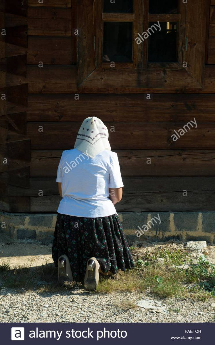 woman-kneeling-in-prayer-on-the-grass-outside-the-church-FAETCR.jpg
