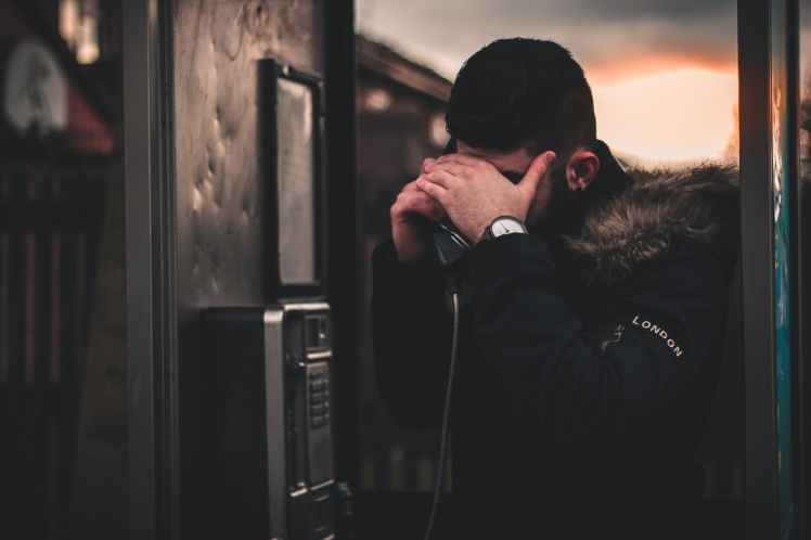 man wearing black parka jacket holding telephone